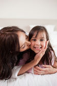 Portrait of a mother kissing her daughter — Stock Photo