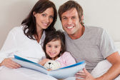 Smiling parents reading a story to their daughter — Stock Photo