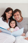 Portrait of parents reading a story to their daughter — Stock Photo