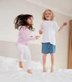 Portrait of siblings jumping — Stock Photo