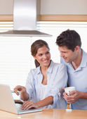 Portrait of a couple using a laptop while having tea — Stock Photo