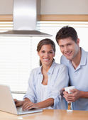 Portrait of a couple using a laptop while having coffee — Stock Photo
