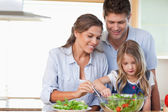 Family preparing a salad — Stock Photo