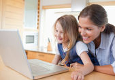 Smiling mother and her daughter using a notebook — Stock Photo