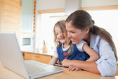 Smiling mother and her daughter using a laptop — Stok fotoğraf