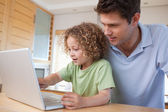 Boy and his father using a notebook — Stockfoto