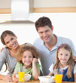 Smiling family having breakfast — Stock Photo