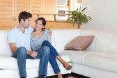Leende par sitter på en soffa — Stockfoto