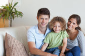 Family sitting on a sofa — Stock Photo