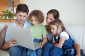 Serene family using a notebook — Stock Photo