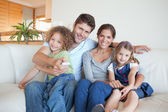 Happy family watching TV together — Stock Photo