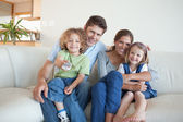 Smiling family watching TV together — Stock Photo