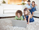 Children using a notebook while their parents are watching — Stock Photo