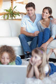 Portrait of parents watching their children using a laptop — Stock Photo