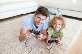 Smiling boy and his father playing video games — Stok fotoğraf