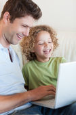 Portrait of a cute boy and his father using a laptop — Stock Photo
