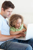 Portrait of a young boy and his father using a laptop — Stock Photo