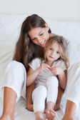 Portrait of a mother and her daughter posing on a bed — Stock Photo