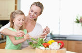 Mother and daughter stirring salad — Stock Photo