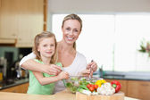 Smiling mother and daughter stirring salad — Stock Photo