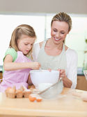 Smiling mother and daughter preparing dough for cookies — Stock Photo