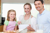Girl preparing dough with her parents — Stock Photo