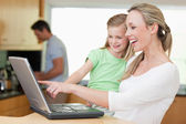 Happy mother and daughter using laptop with father in the backgr — Stock Photo