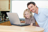 Father and son with notebook in the kitchen — Stockfoto