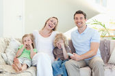 Family laughing on the sofa — Stock Photo