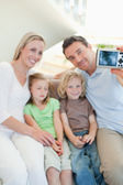 Man taking family picture on sofa — Stock Photo