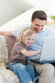 Father and son with notebook on sofa — Stok fotoğraf