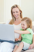 Mother and daughter with laptop on couch — Stock Photo