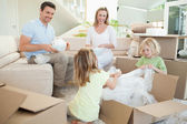 Family unpacking cardboard box in the living room — Stock Photo