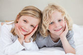Brother and sister lying on the bed — Stock Photo
