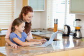 Mother and daughter with laptop in the kitchen — Stockfoto