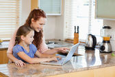 Mother and daughter with laptop behind the kitchen counter — Stock Photo