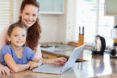 Mother and daughter surfing the internet in the kitchen — Stock Photo