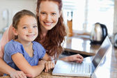 Mother and daughter with notebook in the kitchen — Stockfoto