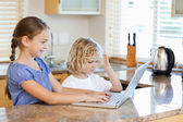 Siblings on the laptop in the kitchen — Stock Photo