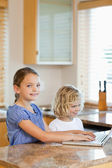 Brother and sister with laptop in the kitchen — Stock Photo