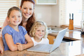 Mother with children on them laptop in the kitchen — Stock Photo