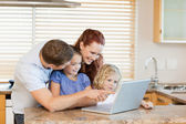Family with laptop in the kitchen — Stock Photo