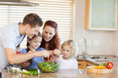 Family preparing salad together — Stock Photo
