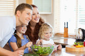 Family together with salad in the kitchen — Stock Photo