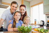 Family standing behind the kitchen counter — Stock Photo