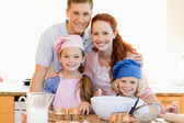 Family with baking ingredients in the kitchen — Stock Photo