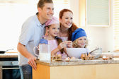 Family in the kitchen with baking ingredients — Stock Photo
