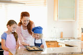 Mother presenting finished cookies to her children — Stock Photo