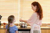 Mother showing her daughter what shes cooking — Stock Photo