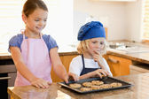 Siblings stealing cookies — Stock Photo